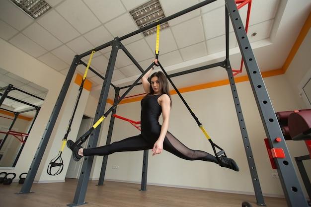 Junge attraktive frau macht splits crossfit stretching mit trx-fitnessgurten im studio des fitnessstudios
