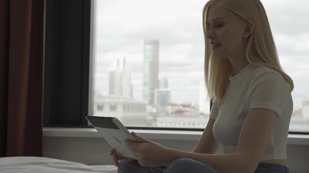Junge attraktive frau macht videoanrufe im schlafzimmer mit einem großen fenster. eine glückliche frau zeigt auf dem video einen wunderschönen blick aus dem fenster der metropole. 4k uhd