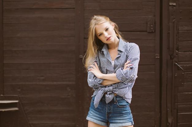 Junge attraktive frau mit blondem haar in hemd und jeansshorts verträumt mit brauner wand lokalisiert
