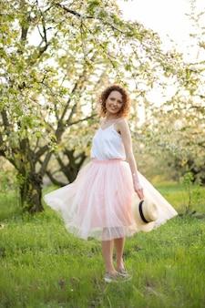Junge attraktive frau mit dem lockigen haar, das in einem grünen blumengarten geht. frühlingsromantische stimmung
