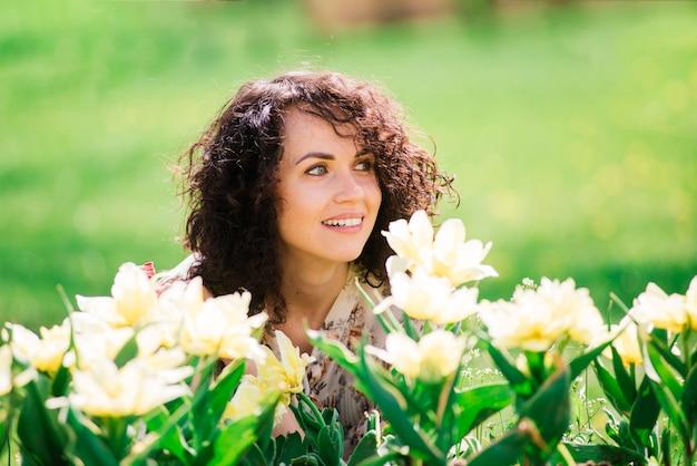Junge attraktive frau mit dem lockigen langen haar, das im blühenden garten des frühlings, apfelbäume aufwirft Premium Fotos