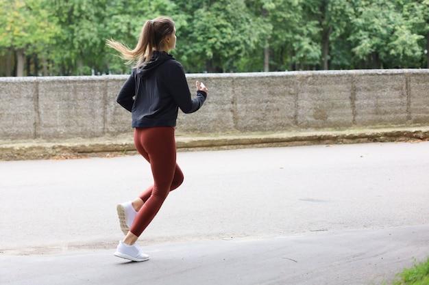 Junge attraktive frau mit dem perfekten schlanken körper, der draußen läuft. fitness- und laufkonzept.