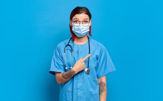 Junge attraktive frau mit rotem haar, die aufgeregt und überrascht aussieht und zur seite und nach oben zeigt, um raum zu kopieren. krankenhauskrankenschwester-konzept