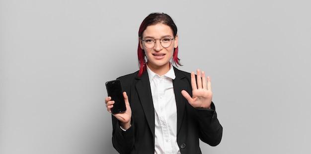 Junge attraktive frau mit rotem haar, die freundlich lächelt und aussieht und nummer fünf oder fünfte mit der hand nach vorne zeigt und herunterzählt. unternehmenskonzept
