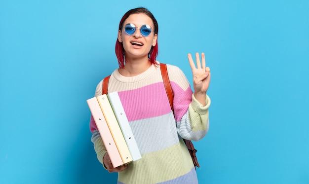 Junge attraktive frau mit rotem haar, die lächelt und freundlich aussieht, nummer drei oder dritte mit der hand nach vorne zeigend, rückwärts zählend. konzept für universitätsstudenten