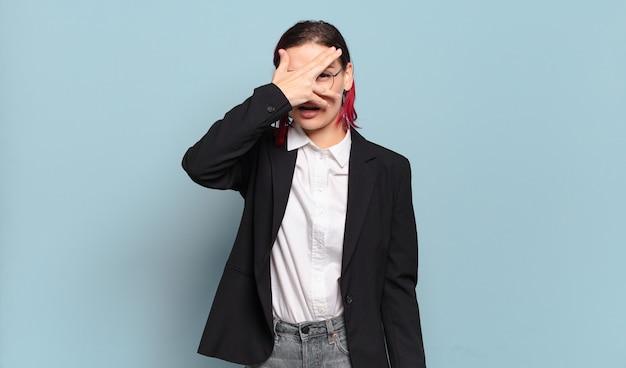 Junge attraktive frau mit rotem haar, die schockiert, verängstigt oder verängstigt aussieht, gesicht mit hand bedeckt und zwischen fingern späht