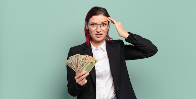 Junge attraktive frau mit roten haaren, die glücklich, erstaunt und überrascht aussieht, lächelt und erstaunliche und unglaublich gute nachrichten realisiert. geldkonzept