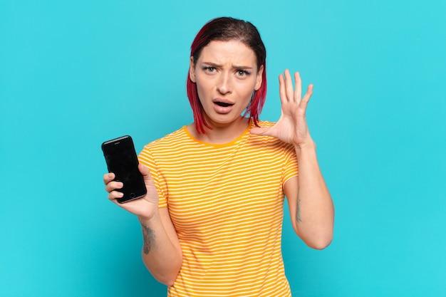 Junge attraktive frau mit roten haaren, die mit den händen in der luft schreit, sich wütend, frustriert, gestresst und verärgert fühlt und ihre zelle zeigt
