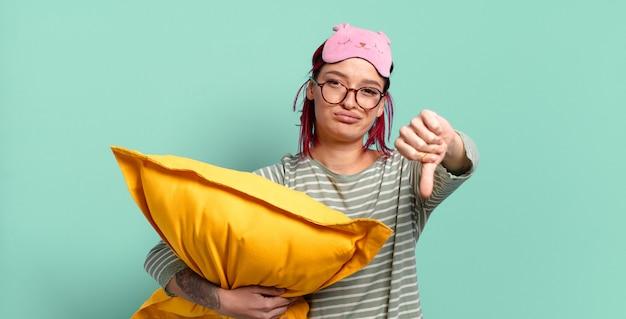 Junge attraktive frau mit roten haaren, die sich böse, wütend, verärgert, enttäuscht oder unzufrieden fühlt, daumen nach unten zeigt und einen pyjama trägt.