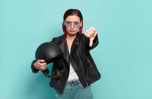 Junge attraktive frau mit roten haaren, die sich böse, wütend, verärgert, enttäuscht oder unzufrieden fühlt und mit einem ernsten blick die daumen nach unten zeigt. motorradfahrer-konzept