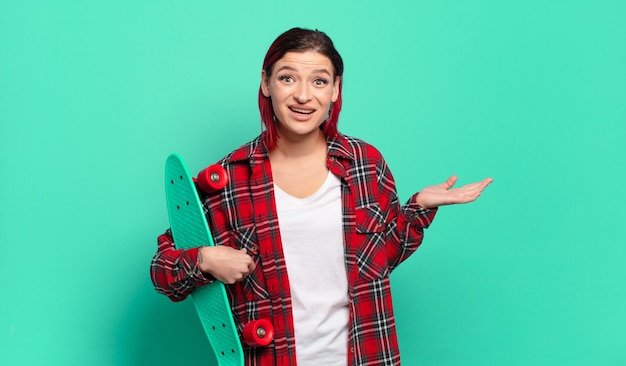 Junge attraktive frau mit roten haaren, die sich glücklich, überrascht und fröhlich fühlt, mit positiver einstellung lächelt, eine lösung oder idee verwirklicht und ein skateboard hält