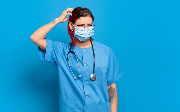 Junge attraktive frau mit roten haaren, die sich verwirrt und verwirrt fühlt, sich am kopf kratzt und zur seite schaut. krankenhauskrankenschwester-konzept