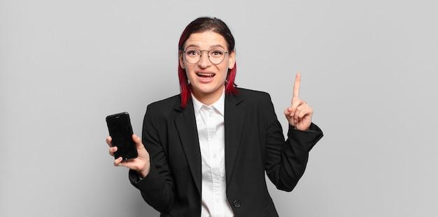 Junge attraktive frau mit roten haaren, die sich wie ein glückliches und aufgeregtes genie fühlt, nachdem sie eine idee verwirklicht und fröhlich den finger hebt, eureka!. unternehmenskonzept