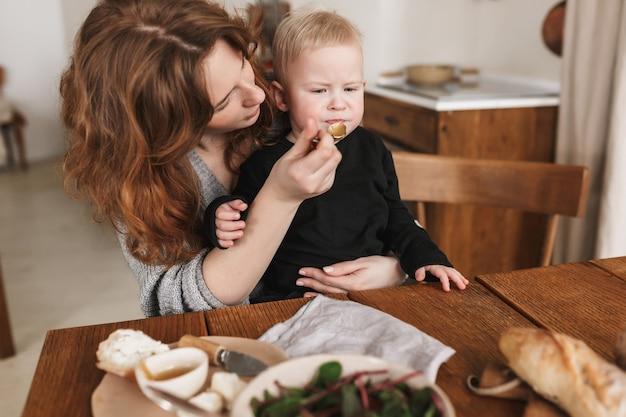 Junge attraktive frau mit roten haaren im gestrickten pullover, der am tisch mit dem essen sitzt, das nachdenklich ihren kleinen sohn füttert