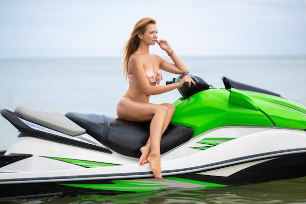 Junge attraktive frau mit schlankem sexy körper im stilvollen bikini-badeanzug, der spaß auf wasserscooter, sommerferien, aktiven sport hat