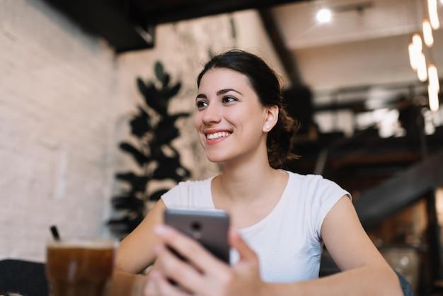Junge attraktive frau mit schönem gesicht und lächeln, die handy hält, anwendung im dachbodencafé herunterladend. blogger schreiben blogposts mit smartphone und internet