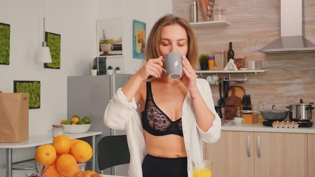 Junge attraktive frau mit tätowierungen in verführerischer unterwäsche, die eine tasse tee in der küche lächelnd hält. sexy blonde dame in der wäsche, die kaffee während des frühstücks trinkt, das den morgen genießt.