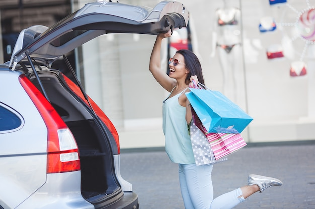 Junge attraktive frau nach dem einkauf. frau, die einkaufstaschen hält und sie in das auto setzt. schöne stilvolle dame im einkaufszentrum.