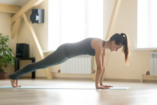 Junge attraktive frau stand in plank pose, home interior bac