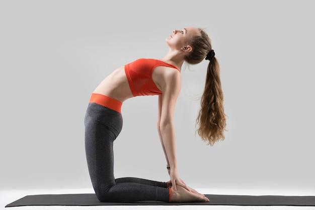 Junge attraktive frau stretching in ustrasana pose, grau studio