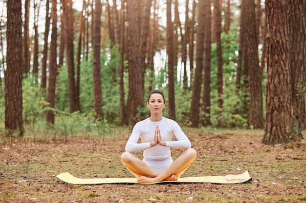 Junge attraktive frau trägt weiße sportkleidung, die auf karemat in lotuspose sitzt sitting