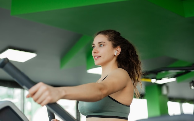 Junge attraktive frau trainiert auf ellipsentrainer im fitnessstudio. fitness, gesunder lebensstil konzept.