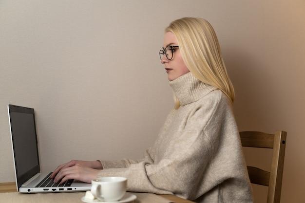 Junge attraktive geschäftsfrau arbeitet hinter einem laptop mit einer tasse kaffee