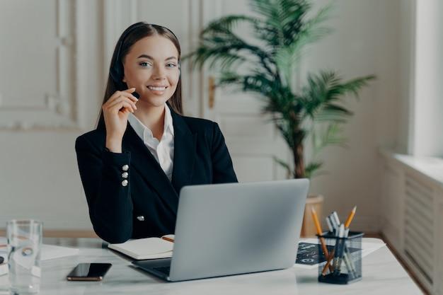 Junge attraktive geschäftsfrau im eleganten anzug mit headset während des online-meetings, arbeitet am laptop im modernen büro. schöne weibliche büroangestellte in formeller kleidung, die an einer webkonferenz teilnimmt
