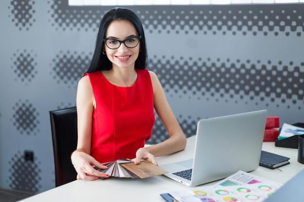 Junge attraktive geschäftsfrau im roten kleid und in den gläsern sitzen am tisch und arbeiten mit laptop und halten holzproben