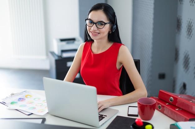Junge attraktive geschäftsfrau im roten kleid und in den gläsern sitzen am tisch und arbeiten mit laptop