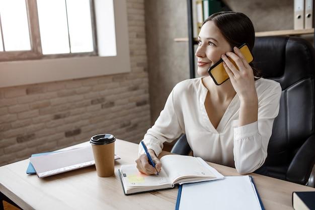 Junge attraktive geschäftsfrau sitzen am tisch im zimmer. sie telefoniert und schreibt in ein notizbuch. modell freuen sich.
