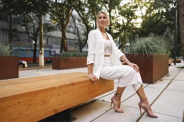 Junge attraktive geschäftsfrau sitzt auf einer holzbank in einer straße