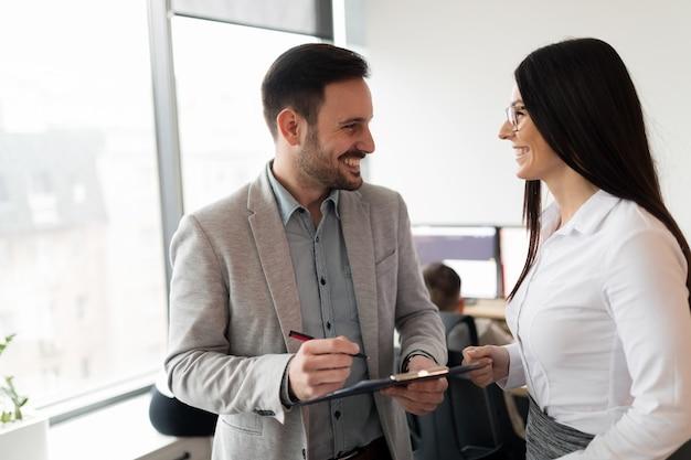 Junge attraktive geschäftspaare mit tablet in ihrer firma