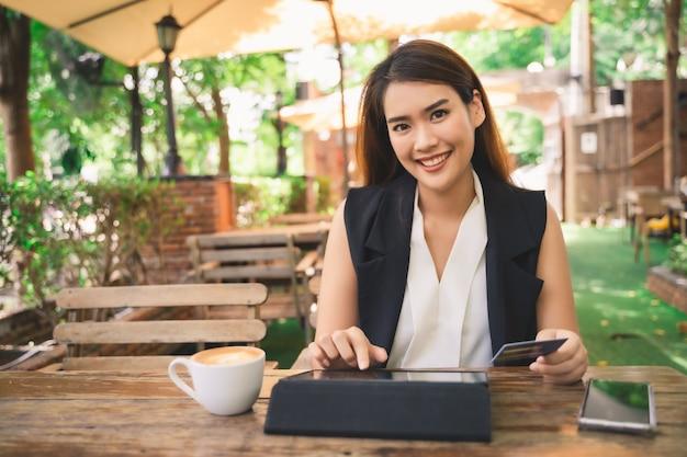 Junge attraktive glückliche asiatin benutzt tablette oder smartphone für das einkaufen und das zahlen online durch debit- oder kreditkarten