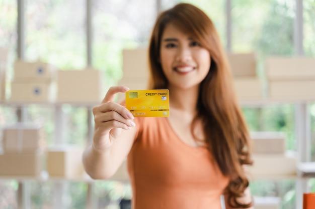Junge attraktive glückliche asiatische frau, die in der hand kreditkarte zeigt