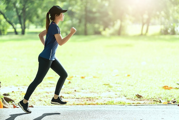 Junge attraktive glückliche asiatische läuferfrau, die öffentlich naturstadt läuft
