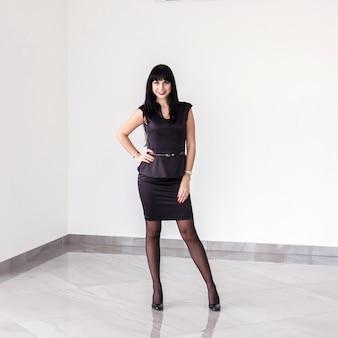 Junge attraktive glückliche brunettefrau mit einem kurzen rock steht gegen die weiße wand im büro
