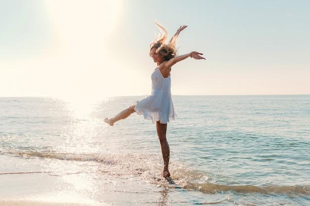 Junge attraktive glückliche frau, die durch sonnigen sommermode-stil des seestrandes sich dreht