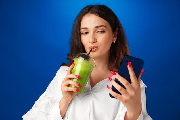 Junge attraktive glückliche frau, die eine tasse grünen smoothie hält und ihr smartphone gegen blaues...