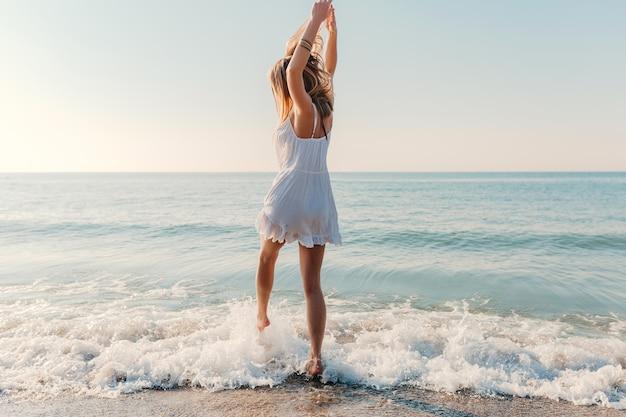 Junge attraktive glückliche frau, die sich am sonnigen sommermode-stil des seestrandes im urlaub des weißen kleides umdreht