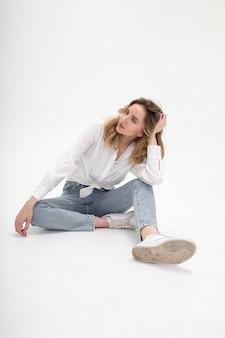 Junge attraktive kaukasische blonde frau, die im hemd und in den blauen jeans, die auf weißem studioboden sitzt, aufwirft