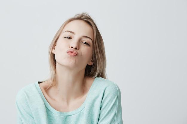 Junge attraktive kaukasische frau gekleidet in der blauen freizeitkleidung, die mit kuss auf den lippen mit blond gefärbtem haar aufwirft, das flirty blick sicher und schön fühlt. charmante frau, die drinnen spaß hat
