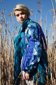 Junge attraktive kaukasische frau in jacke am feld an einem sonnigen tag vor trockenem gras und blauem himmel