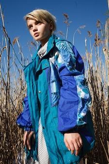 Junge attraktive kaukasische frau mit kurzen haaren in blauer jacke an einem sonnigen tag