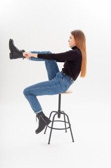 Junge attraktive kaukasische frau mit langen haaren im schwarzen rollkragenpullover, blaue jeans auf weißem hintergrund