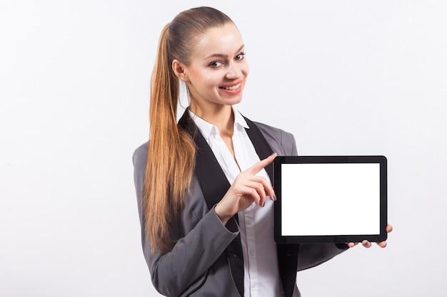 Junge attraktive kaukasische geschäftsfrau in der leeren tablette des grauen klagengriffs