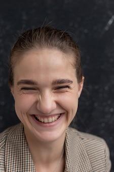 Junge attraktive kaukasische lächelnde frau mit braunem haar in anzugjacke