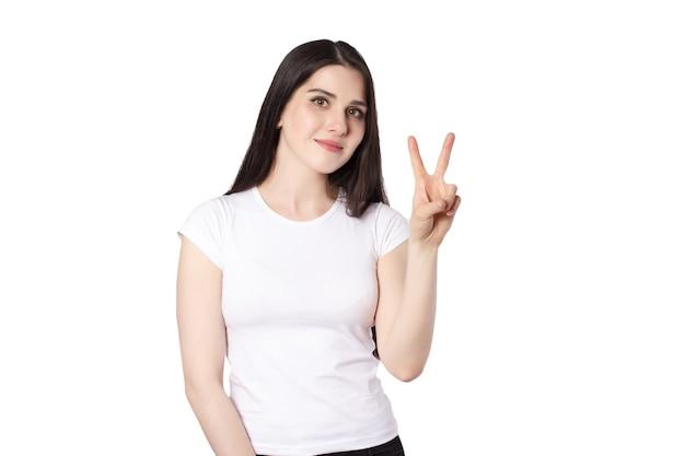 Junge attraktive kaukasische langhaarige brünette lächelnde frau im weißen t-shirt auf weißem hintergrund, erhobene hände, friedensgeste bieten konzeptidee