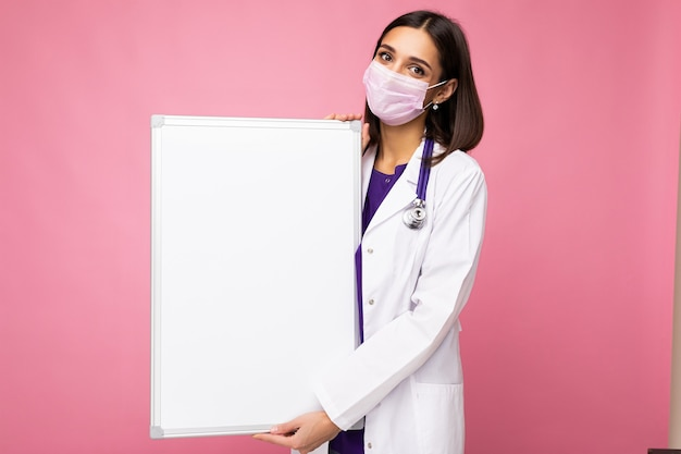 Junge attraktive krankenschwester in schützender gesichtsmaske und weißem medizinischem kittel, die eine leere magnettafel auf rosafarbenem hintergrund hält