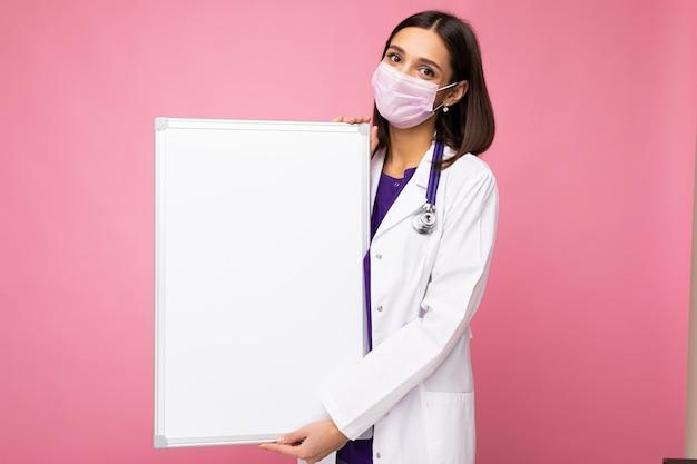 Junge attraktive krankenschwester in schützender gesichtsmaske und weißem medizinischem kittel mit leerem magnet